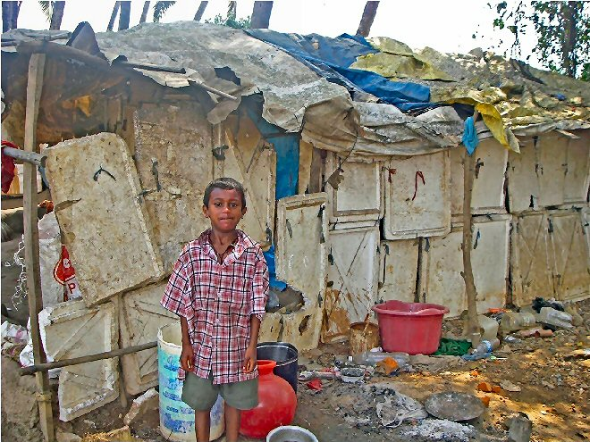 Boy outside his Indian slum home