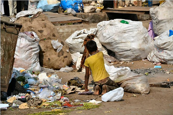 destitute Indlan boy collecting rags from the rubbish tip